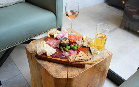 Wooden cutting board with sliced cheeses & cold cuts with wine glasses