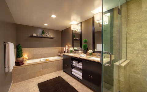 Bathroom with marble tile flouring and walls, dark wooden cabinets under sink & glass shower