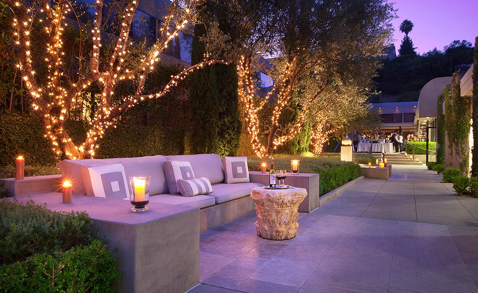 Outdoor seating with cushions next to trees lit up with Christmas lights