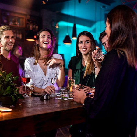 Friends gathered around table with drinks at bar