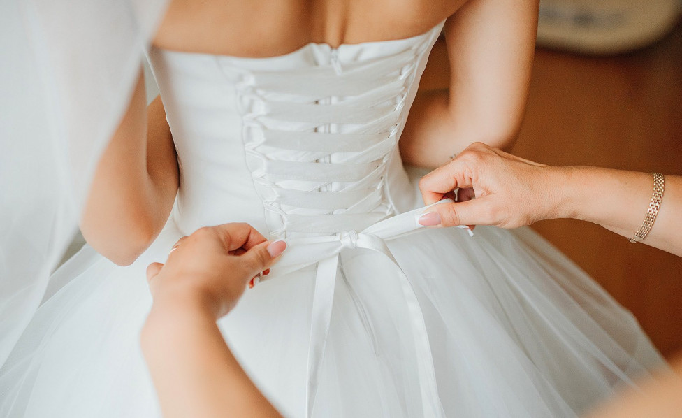 Close up of someone helping bride tie a knot on the back of dress Inset