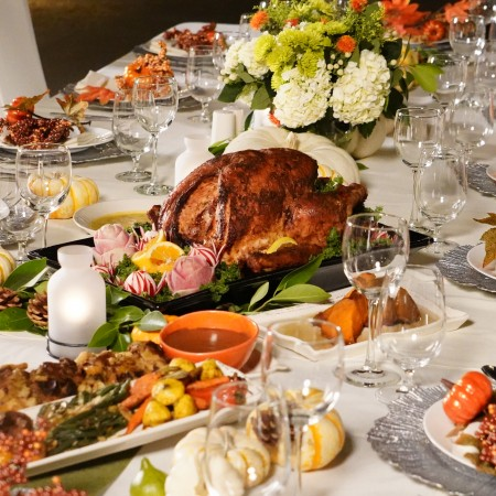 Table set up for Thanksgiving Dinner with a cooked turkey in the middle decorate with fall-colored flowers