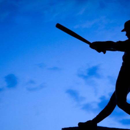 silhouette hitting baseball against blue backdrop