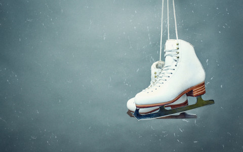 ice skates dangling against grey backdrop