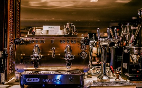 espresso machine with small white coffee cups on top. To the right is 3 beer taps and other appliances are blurred in the background