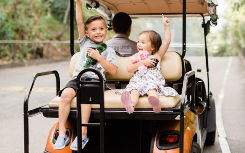 two kids sitting on back of a golf cart pointing up into the sky