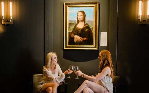 two women toasting wine glasses under mona lisa painting