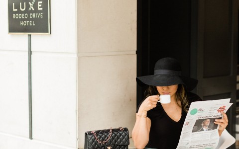 woman sipping espresso outside luxe rodeo hotel reading newspaper