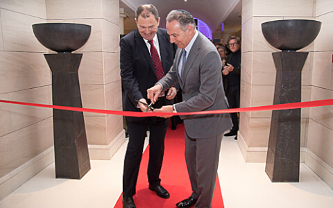 two men cutting red ribbon with scissors