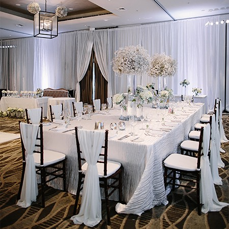 wedding venue decorated with white table, centerpieces, and draping