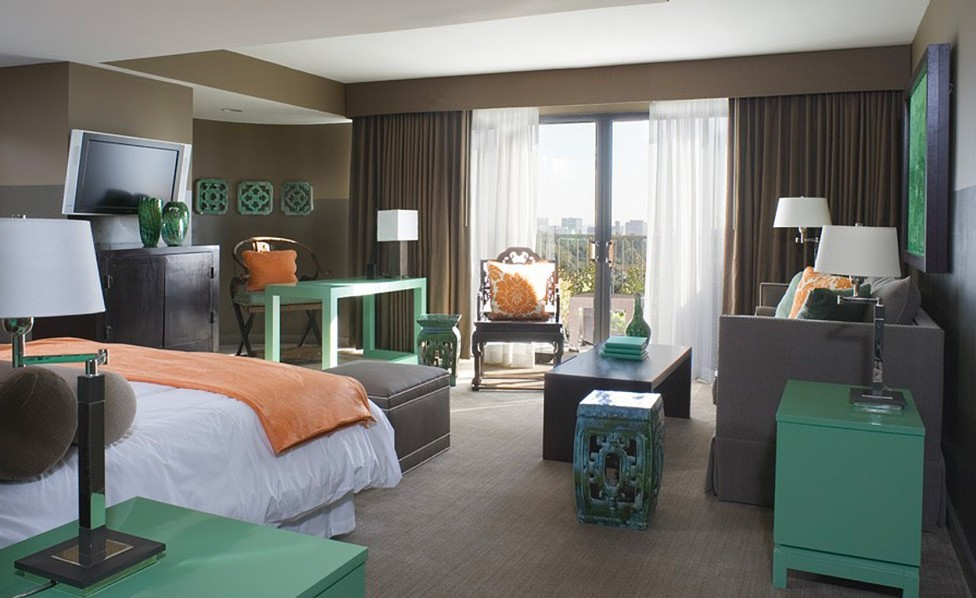 Vista Suite with light green accent furniture and orange pillow and blankets with a balcony, couch, desk, bed and TV