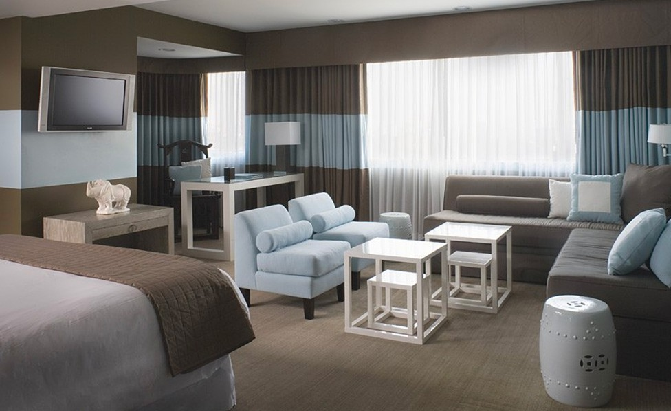 Vista Suite with light blue accent chairs and light blue strip painted on the wall and on the curtains with brown couch and blanket with bed, TV, desk and couch