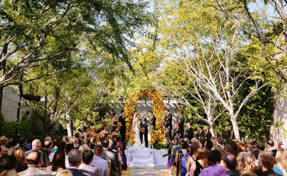 outdoor wedding ceremony with a yellow floral arch Inset