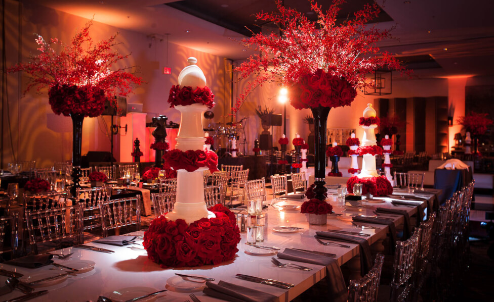 tall red floral centerpieces in spacious reception space Inset