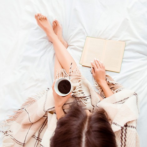 girl sitting on bed with coffee and book