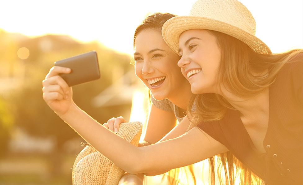 two girls smiling and taking a selfie