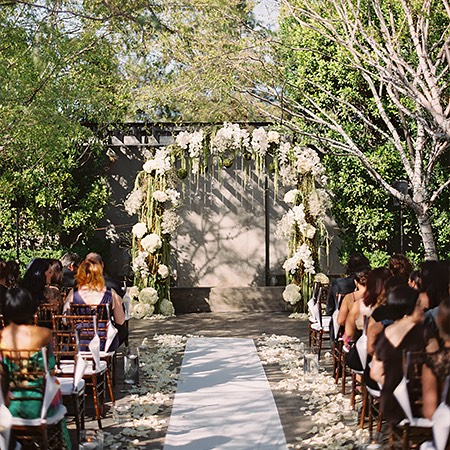 outdoor wedding ceremony set up with flower arch at the end of the aisle