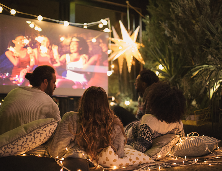 group of friends sitting on a blanket watching a movie outside on a projector with string lights hanging outside