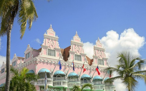 Pink building with blue balcony shades & flags