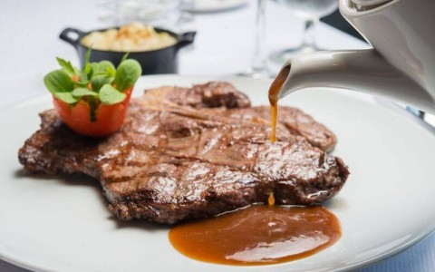 Steak with sauce being poured from The Chophouse