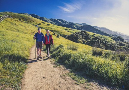 older couple hiking on a hilltop walking trail