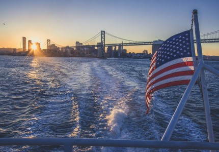 view from the back of a boat with an american flag and the golden gate bridget in the background
