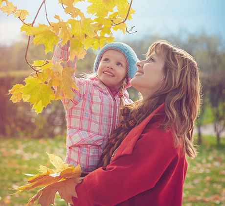 woman and baby looking at autumn leaves