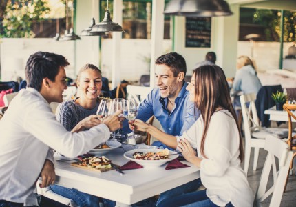 group of friends clinking glasses at dinner