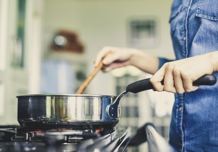 woman cooking on a stove with a pot and wooden spoon