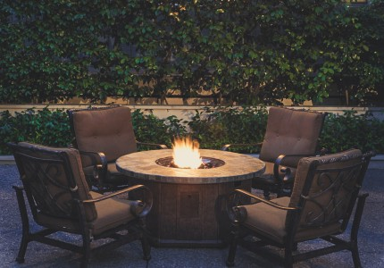 patio table with a firepit and greenery