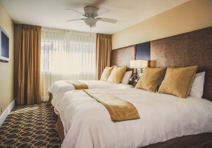 guestroom with double queen beds with white and gold bedding