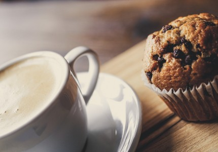 close up of a coffee cup and muffin