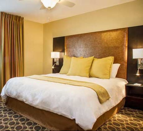 guestroom with king bed with white and gold bedding