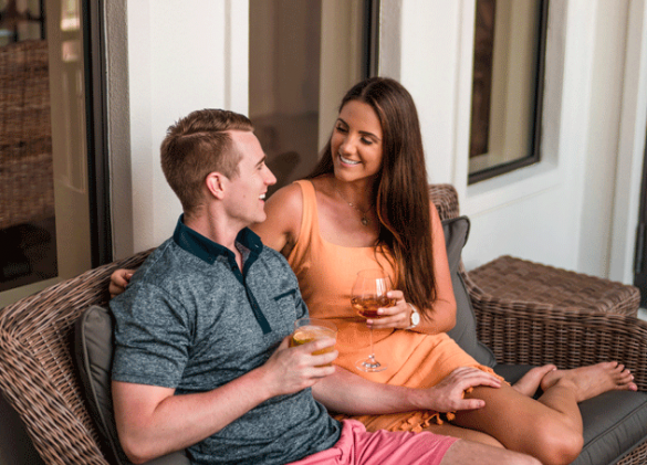couple relaxing on a patio couch and enjoying drinks