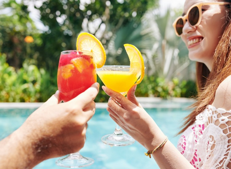couple toasting with tropical drinks outside by pool