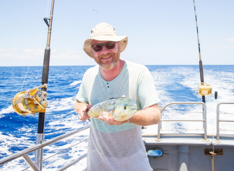 man holding fresh caught mahi mahi on ocean boat