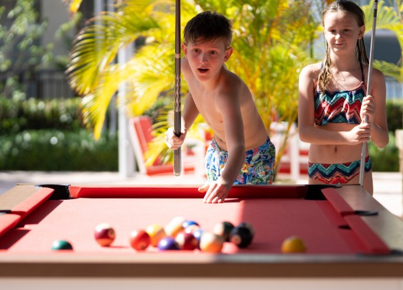 two kids playing a game of pool