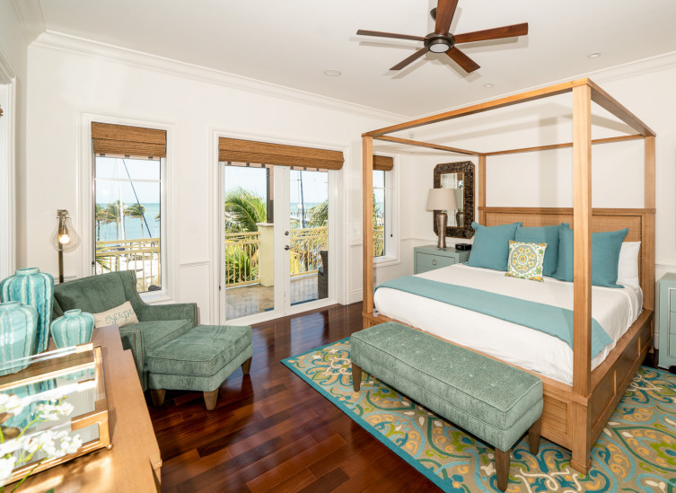 Room with King bed & large wooden frame, mint nightstands & lounging chair next to balcony