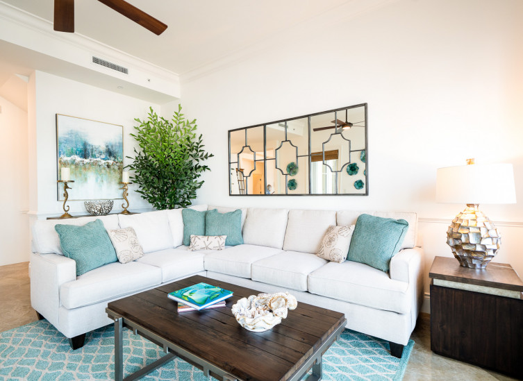 room living space with white sectional, aqua throw pillows & rug