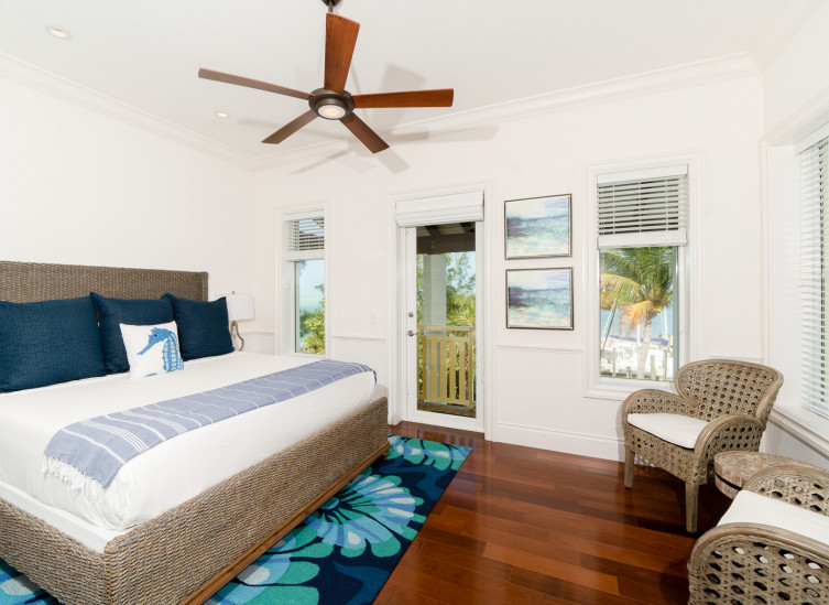 Room with king wicker bed frame, coral design rug & door to balcony