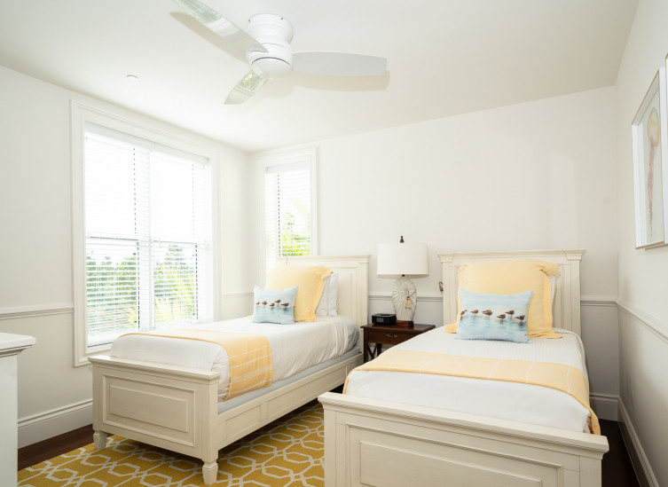 Room with two twin beds with yellow linens & ceiling fan
