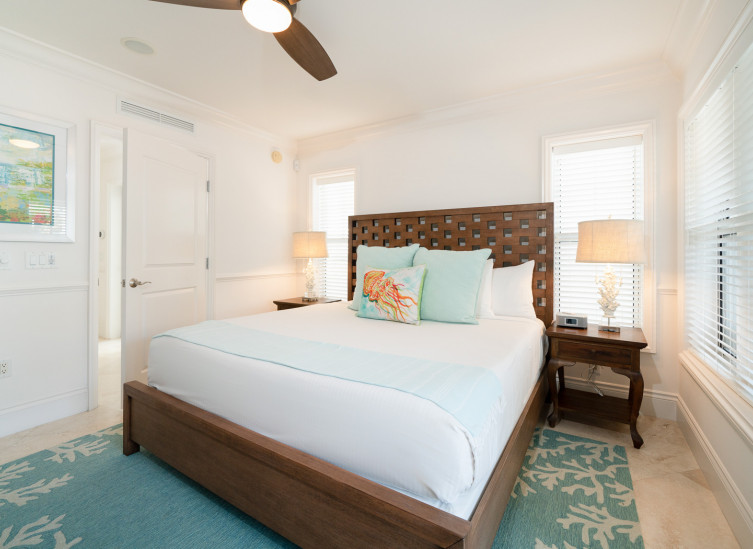 Room with double bed, wooden bed frame, sea themes rug & accent throw pillows