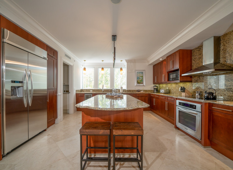Full kitchen with wooden cabinets, kitchen island & steel appliances