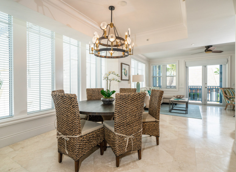 Dining table with wicker chairs next to living area