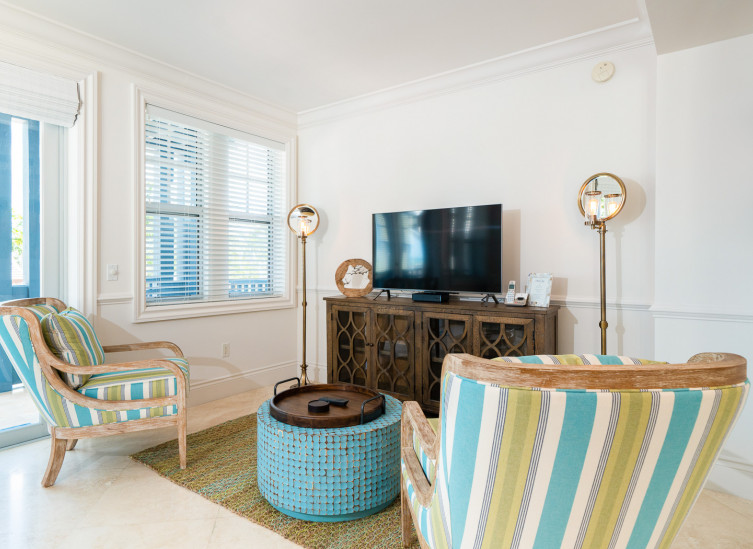Living space with colorful chairs, blue tile coffee table & tv