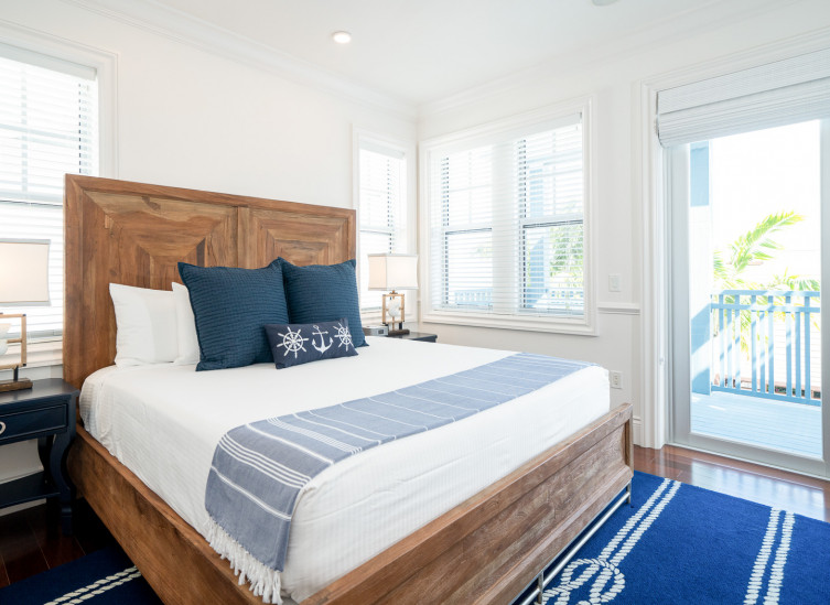 Room with double bed, wooden bed frame, dark blue rug & door leading to balcony