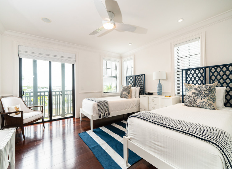Room with two twin beds, striped rug in between them & white furniture