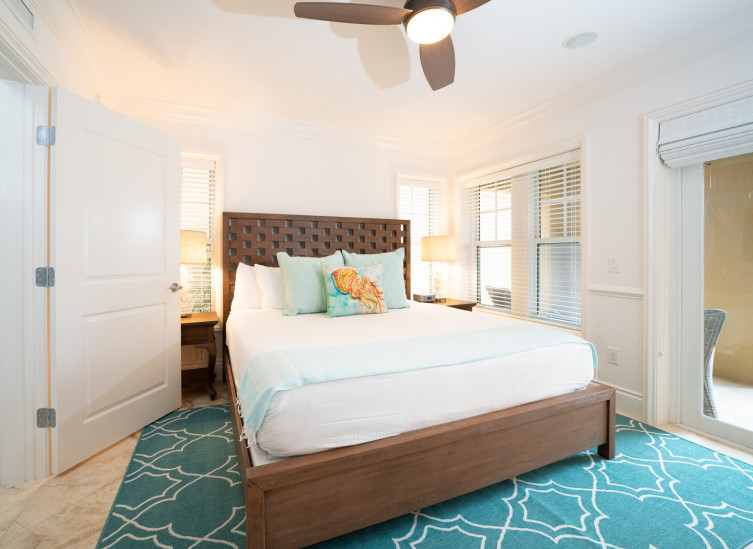 Room with king bed, wooden bed frame, aqua rug & door leading to balcony
