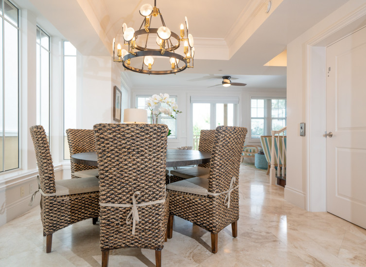 Dining table with wicker chairs under chandelier