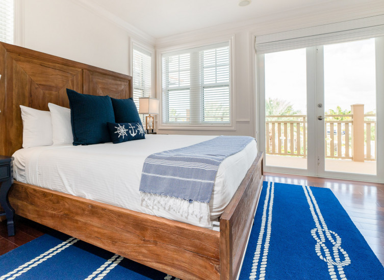 Room with double bed, wooden frame & deep blue rug
